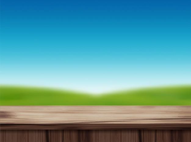 Holztischplatte und unscharfe landschaft des blauen himmels