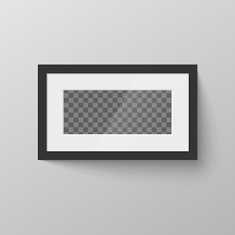 Horizontaler schwarzer leerer bilderrahmen mit transparentem platz für foto an wand