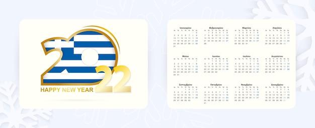 Horizontaler taschenkalender 2022 in griechischer sprache. neujahr 2022-symbol mit flagge griechenlands.