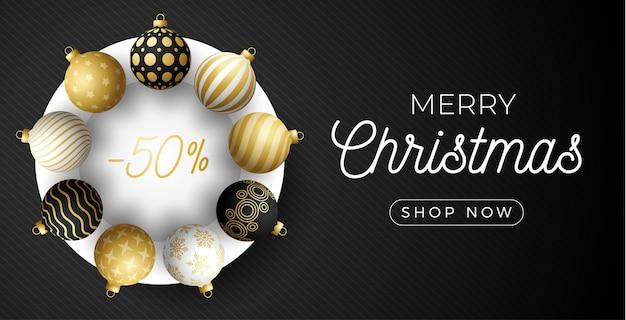 Horizontales banner des luxusweihnachtsverkaufs. weihnachtskarte mit verzierten realistischen kugeln schwarz, gold und weiß auf weißem kreis und schwarzem modernem hintergrund. illustration. platz für ihren text