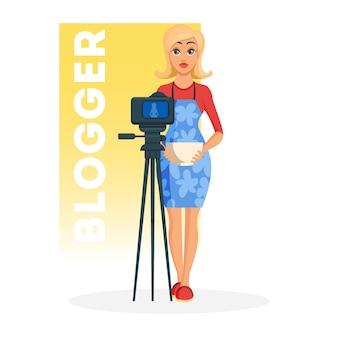 Hübsche blonde junge frau in der blauen schürze, die mit schüssel vor kamera steht. hausfrau, köchin, köchin, die ein video über das kochen aufzeichnet und ein neues rezept für ihren vlog zeigt.