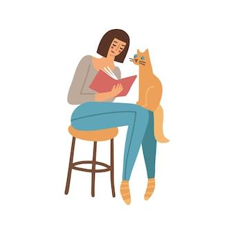 Hübsche frau liest ein buch auf dem hocker und die katze sitzt auf ihren knien