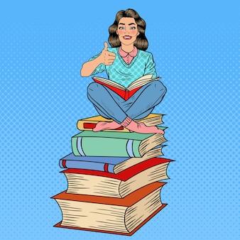 Hübsche pop-art junge frau, die auf dem stapel der bücher sitzt und buch mit handzeichen daumen hoch liest. illustration