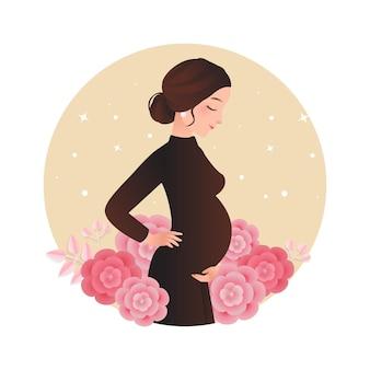 Hübsche schwangere frau, die mit babybauch aufwirft, der mit blumen verziert wird