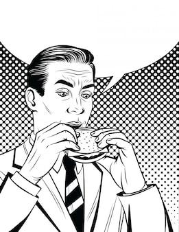 Hübscher erwachsener mann im anzug, der mittagspause mit ungesundem essen hat