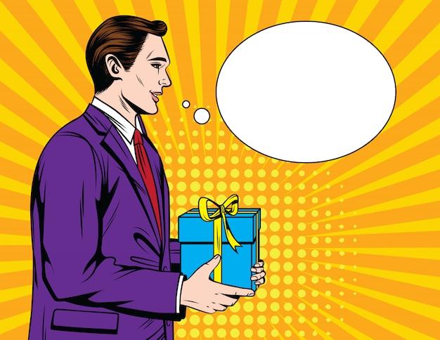 Hübscher glücklicher kerl im anzug, der ein geschenk gibt