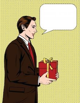 Hübscher glücklicher kerl von 50-60s mit sprechblase, die ein geschenk gibt