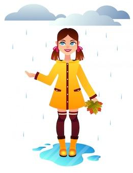 Hübsches süßes kleines mädchen, das gelben regenmantel und gummiboote trägt