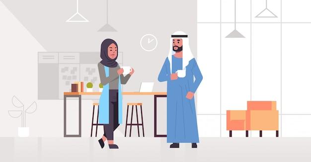 Ic geschäftsleute paar trinken cappuccino arabischen geschäftsmann frau diskutieren während des treffens kaffeepause konzept moderne büro lounge bereich innenraum in voller länge horizontal