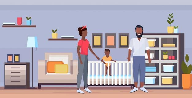 Ihre mutter und ihr neugeborenes baby in der krippe haben spaß zusammen glücklich afroamerikaner familienelternschaft konzept modernes baby schlafzimmer interieur in voller länge horizontal