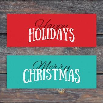 Illustration von bunten papierkarten mit frohen feiertagen und frohen weihnachten beschriftung. weihnachtskalligraphie auf holzhintergrund.