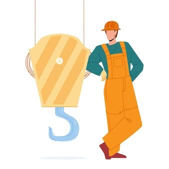 In der nähe von kranhaken bleiben bauarbeiter vektor. mann-erbauer, der uniform trägt, bleibt in der nähe von kranhaken, baumaschinenteil. charakter-ingenieur oder ausrüstungsbediener-flache karikatur-illustration