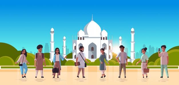 Indische männerfrauengruppe, die zusammen stehend diskutieren, während sie leute in freizeitkleidung der muslimischen nabawi-moschee diskutieren, die stadtbildhintergrund horizontale flache volle länge baut