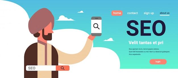 Indischer mann, der das suchmaschinenoptimierungsinternet des smartphone seo sucht konzept verwendet