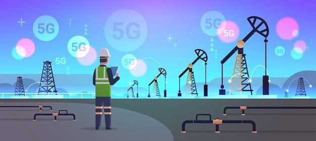 Ingenieur raffineriearbeiter mit tablet 5g online-verbindung für drahtlose systeme ölpumpenanlage energie industriezone ölbohrung produktionskonzept für fossile brennstoffe horizontal in voller länge