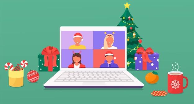 Innenraum des weihnachts- und neujahrsheimarbeitsplatzes mit weihnachtsbaum und dekorationen, geschenken, zuckerrohrkeksen und süßigkeiten, kaffee, laptop. kollegen sprechen über einen videoanruf auf einem laptop-bildschirm miteinander.