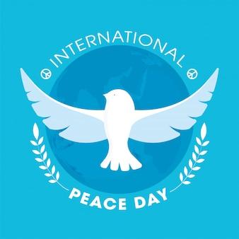 Internationaler friedenstag text mit fliegenden tauben- und blattzweigen auf blauem erdkugelhintergrund.