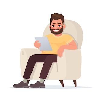 Internetsucht. zeitverschwendung in sozialen netzwerken. ein mann hält eine tablette auf der couch.