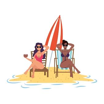 Interracial mädchen entspannen am strand sitzen in stühlen und regenschirm