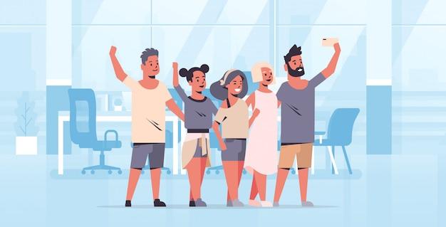 Jugendgruppe, die selfie-foto auf smartphone-kamerakollegen macht, die zusammen moderne büroinnenausstattung in voller länge horizontal stehen