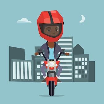 Junge afrikanische frau, die ein motorrad nachts reitet.