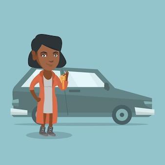 Junge afrikanische frau, die schlüssel zu ihrem neuwagen hält.