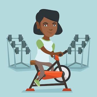 Junge afrikanische frau, die stationäres fahrrad fährt.