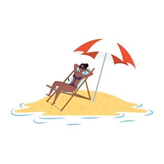Junge afro-frau, die auf dem strand sitzt, der im stuhl und im regenschirm sitzt