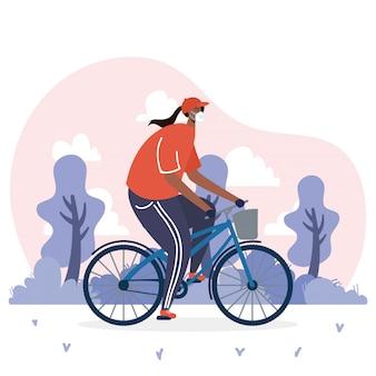 Junge afro-frau, die medizinische maske im fahrrad trägt