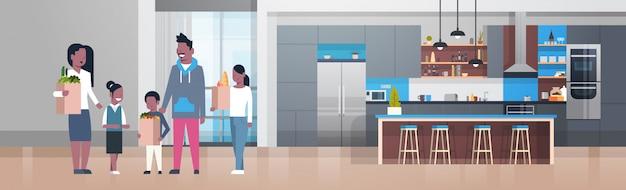 Junge afroamerikaner-familie, die taschen mit lebensmittelgeschäft-produkten im küchenraum hält