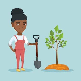 Junge afroamerikanerfrau, die einen baum pflanzt.