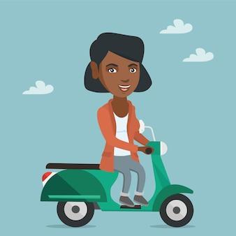 Junge afroamerikanerfrau, die einen roller reitet.