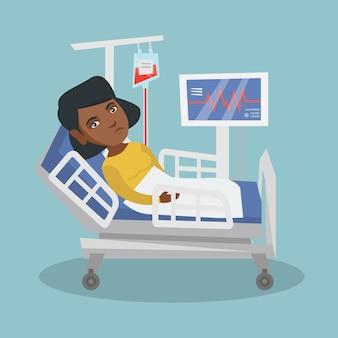 Junge afroamerikanerfrau, die im krankenhausbett liegt