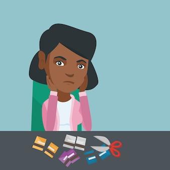 Junge afroamerikanerfrau, die kreditkarten schneidet.