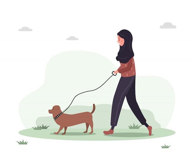 Junge arabische frau im hijab geht mit hund durch den wald. konzept glückliches mädchen im gelben kleid mit dackel oder pudel. vektorillustration im flachen stil.