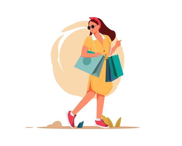 Junge attraktive modische frau, die nach dem einkauf pakete mit kleidung hält