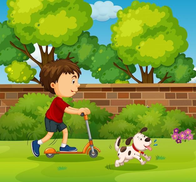 Junge, der auf roller im yard reitet