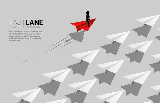 Junge, der auf rotem origami-papierflugzeug steht, bewegt sich schneller als gruppe von weiß