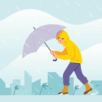 Junge, der durch großen sturm mit regenschirm geht