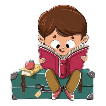 Junge, der ein buch sitzt auf einem koffer liest
