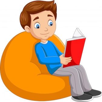 Junge, der ein buch sitzt auf großem kissen liest