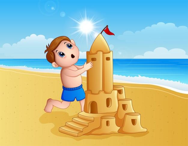 Junge, der ein großes sandburg am strand bildet Premium Vektoren