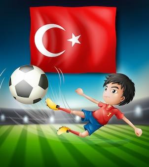 Junge, der einen fußball vor türkischer flagge tritt