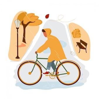 Junge, der fahrrad im herbstpark im regen reitet