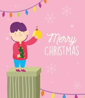Junge der frohen weihnachten im geschenk mit ball- und lichtdekoration