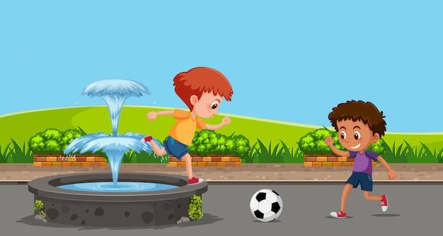 Junge, der fußball am garten spielt