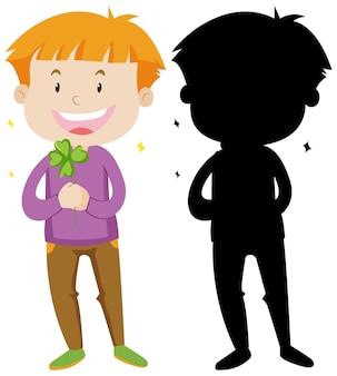 Junge, der kleeblatt in farbe und schattenbild hält