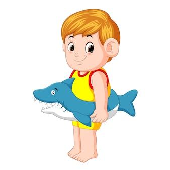 Junge, der mit aufblasbarem ring des haifischs spielt