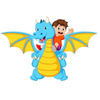 Junge, der mit dem großen blauen drachen spielt und es kann das feuer produzieren