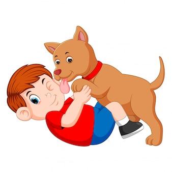 Junge, der mit dem hund und hund spielt, die sein inhabergesicht lecken